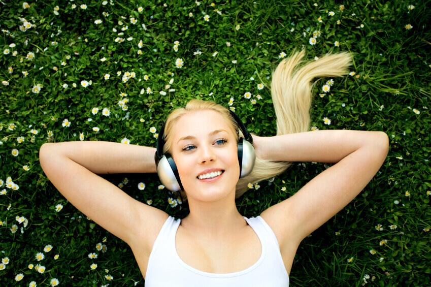 Woman enjoying greenery and listening to music.