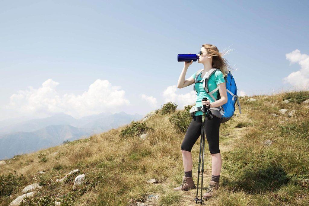 Woman hiker having a cool refreshing drink.
